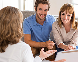 a young couple meeting with a realtor